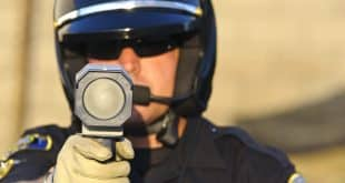 a police officer aiming his radar gun at traffic.