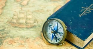 The Compass Beside A Blue Book With A Cross On The Cover. The Co