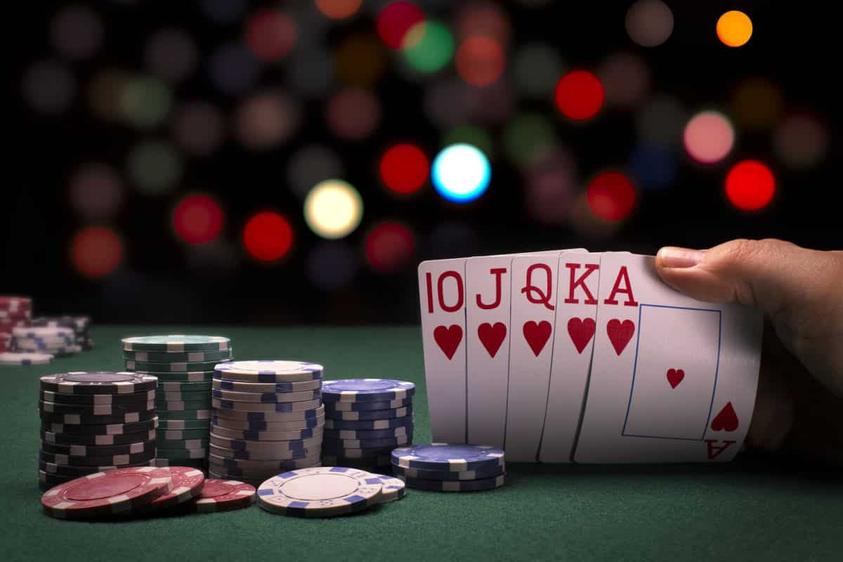 A close up view of a poker hand and poker chips in a casino like setting.