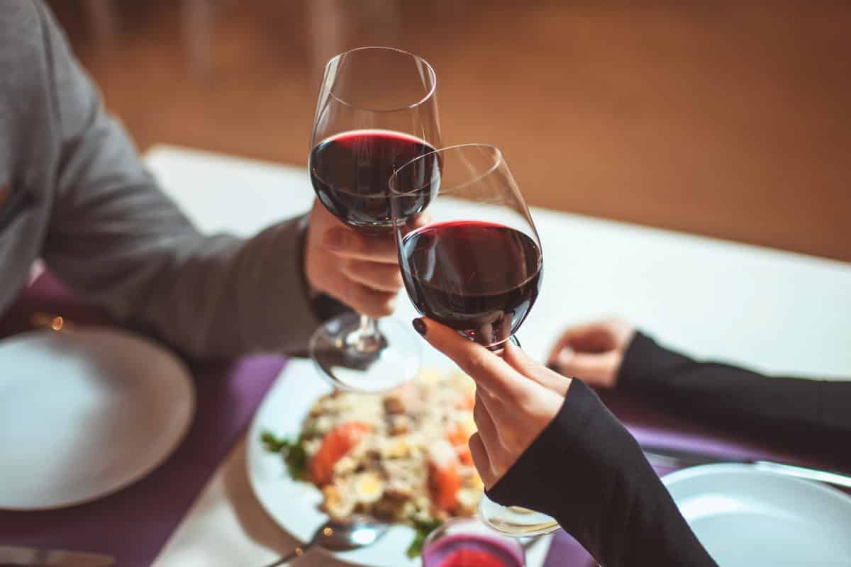 Beautiful Young Couple With Glasses Of Red Wine In Luxury Restau