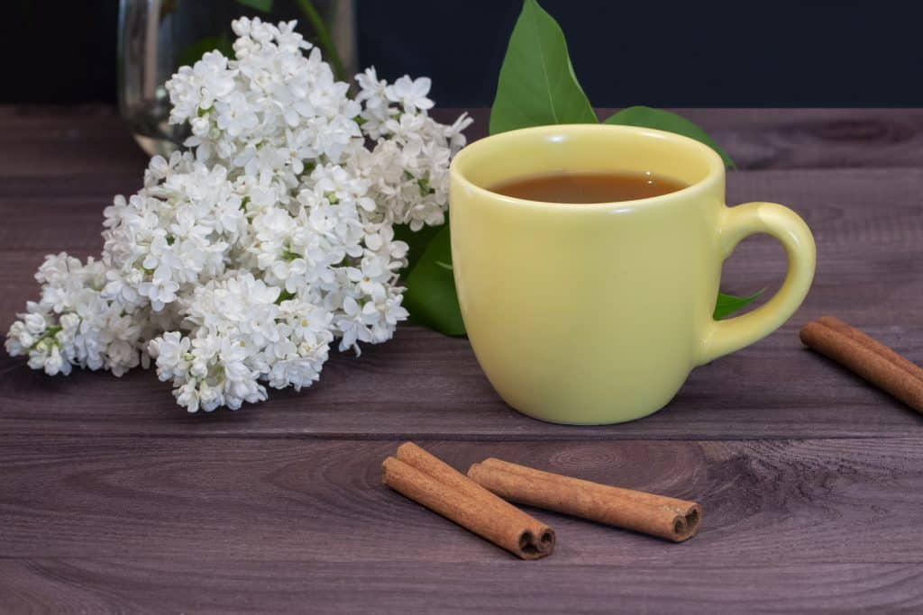 Yellow cup of tea with cinnamon
