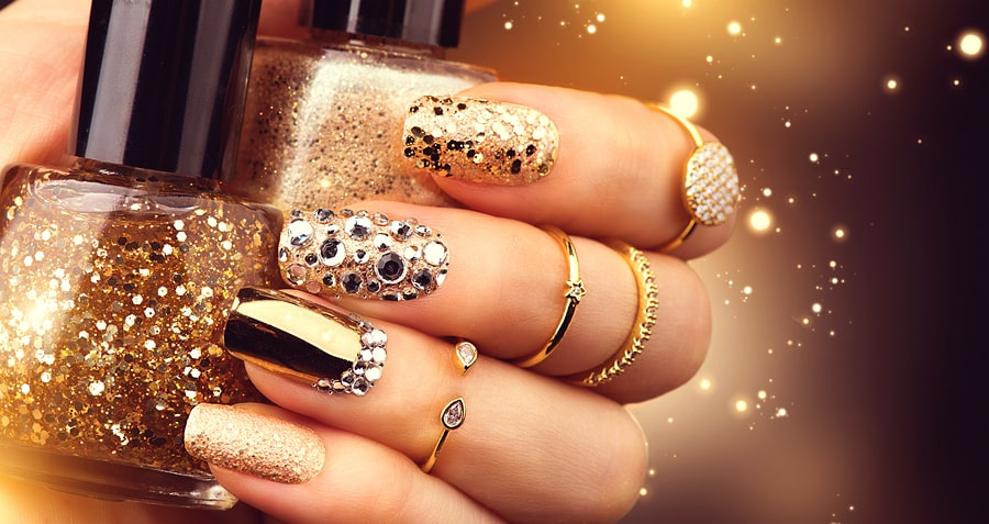 Golden Nail art manicure. Holiday style bright Manicure with gems and sparkles. Bottle of Nail Polish. Fashion rings with diamonds, Trendy Accessories. Beauty hands. Stylish Nails, Nailpolish