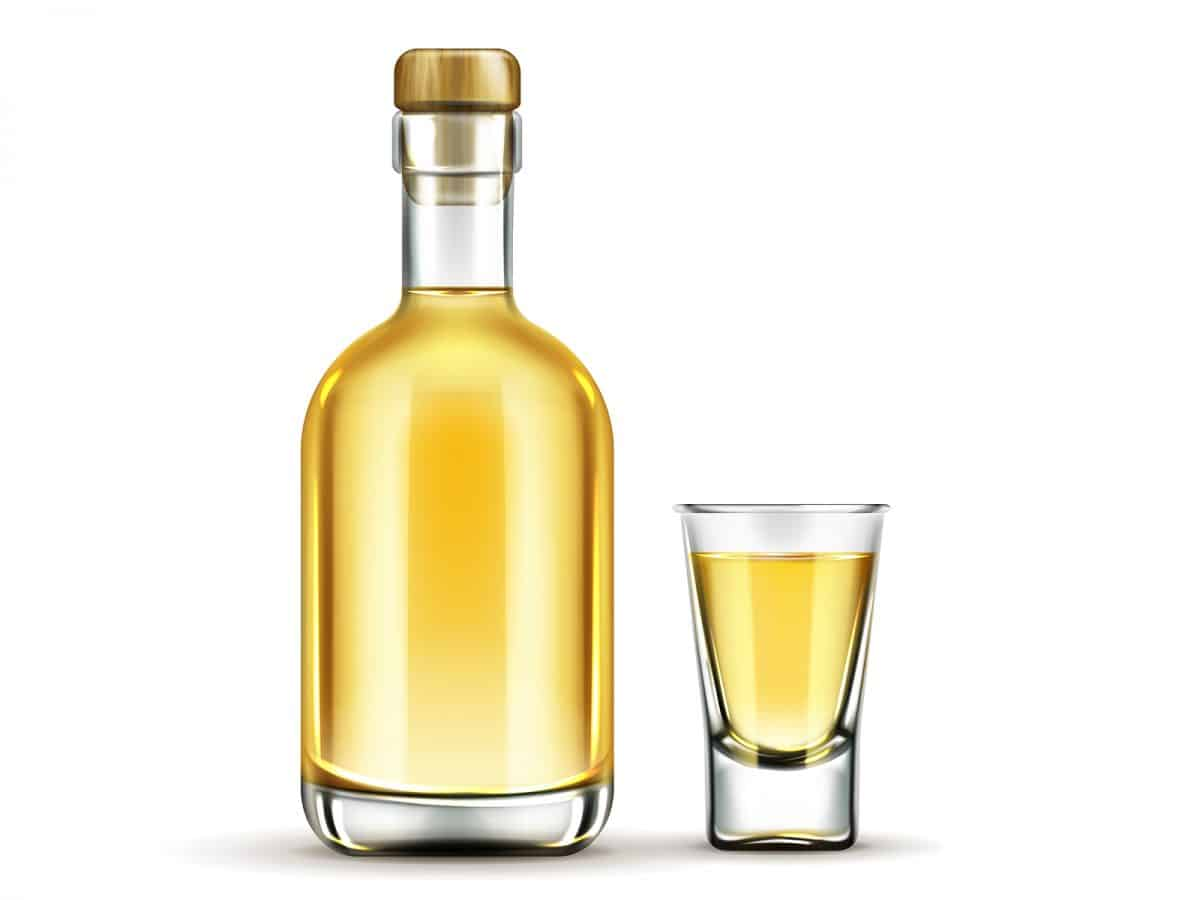 Tequila bottle and shot glass with gold liquid