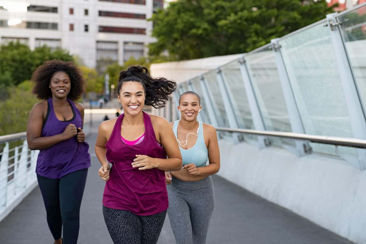 Happy young curvy women jogging together on city bridge.