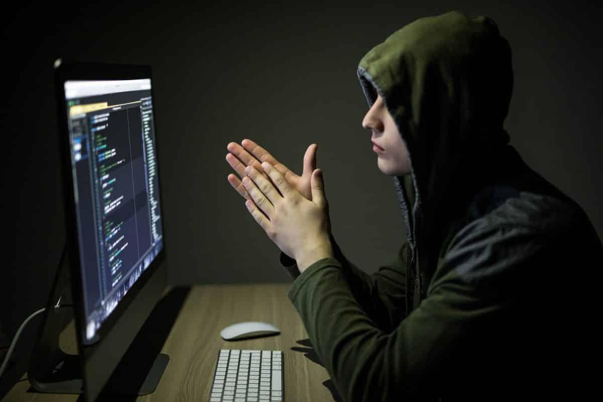 Hacker in glasses breaking code