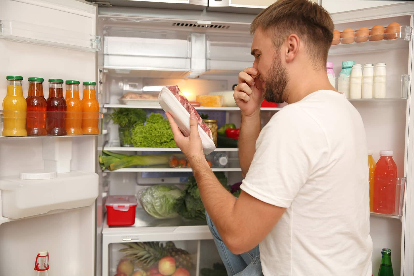 bad smelling meat near refrigerator in kitchen