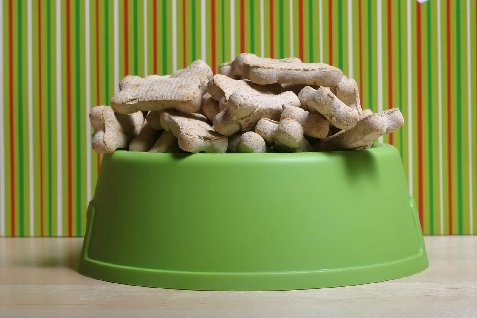 dog treats over-flowing in green dog bowl