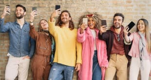 Happy group friends taking selfie with cell phone outdoo