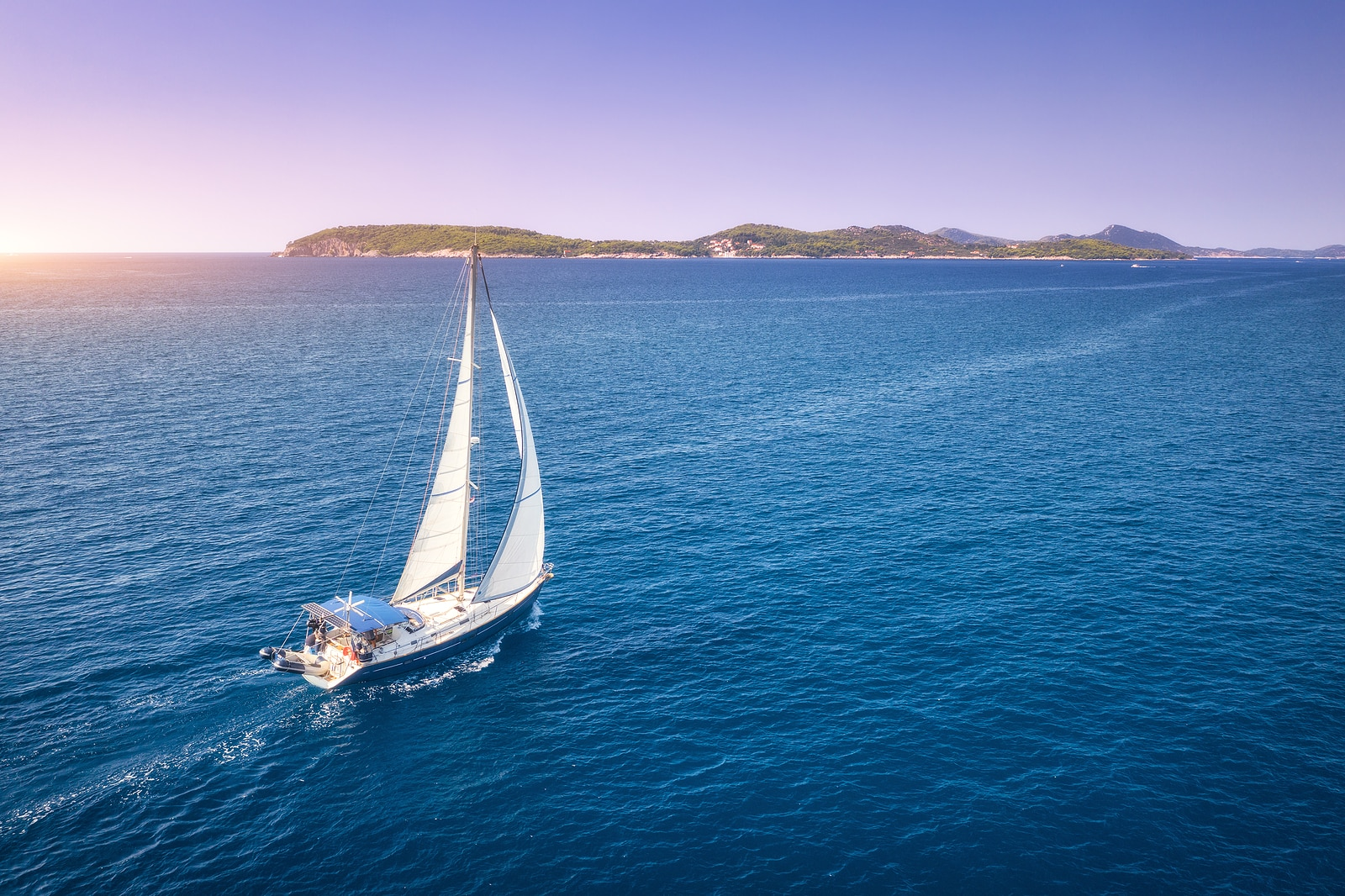 Aerial view of beautiful white sailboat in blue sea
